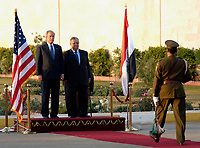 Baghdad, Iraq - December 14, 2008 -- United States President George W. Bush and President Jalal Talabani of Iraq stand between the United States and Iraq flags  Sunday, December 14, 2008 before the playing of the U.S. national anthem. Bush is on his final visit to Iraq before the end of his second presidential term to meet with Iraqi leaders and sign a ceremonial copy of the security agreement.<br /> CAP/MPI/CNP/RS<br /> &copy;RS/CNP/MPI/Capital Pictures