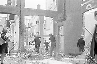Photo from the NIOD's Huizinga collection. A group of people illegally demolishes firewood from vacant buildings during the fuel shortage caused by the national railway strike.