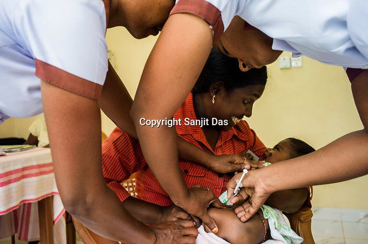 Government health workers vaccinate an infant at the government health centre in Tharmapuram in North Kilinochchi, Sri Lanka.  Photo: Sanjit Das/Panos