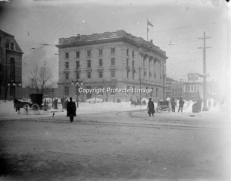 UNITED STATES COURTHOUSE AND POST OFFICE, LINCOLN, 1910-1915. No single building figures more prominently in John Johnson's photographs than the new downtown post office at the center of this snowy view of Government Square. The building at the left was the earlier courthouse and post office, built in the 1870s. The federal government sold &quot;Old City Hall&quot; to the City of Lincoln, which used it as the seat of municipal government from 1905 to 1969.<br /> <br /> Photographs taken on black and white glass negatives by African American photographer(s) John Johnson and Earl McWilliams from 1910 to 1925 in Lincoln, Nebraska. Douglas Keister has 280 5x7 glass negatives taken by these photographers. Larger scans available on request.