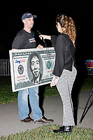 """A reporter interviews Jason Sherfey as he holds a home-made $1000 bill featuring a portrait entrepreneur and Democratic presidential candidate Andrew Yang after the candidate spoke to a large crowd in Cambridge Common near Harvard Square in Cambridge, Massachusetts, on Mon., September 16, 2019. Yang's unlikely presidential bid is centered on his idea for a """"Freedom dividend,"""" which would give USD$1000 per month to every adult in the United States. After appearing in three Democratic party debates, Yang has risen in polls from longshot candidate to within the top 10. Sherfey said that the Los Angeles Yang Gang produced the Yangbucks and he just blew up the design."""