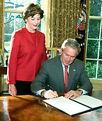 United States President George W. Bush (seated) and first lady Laura Bush participate in the signing of the Presidential Proclamation in Honor of American Heart Month in the Oval Office of the White House in Washington, DC on February 1, 2006.<br /> Credit: Ron Sachs / Pool via CNP