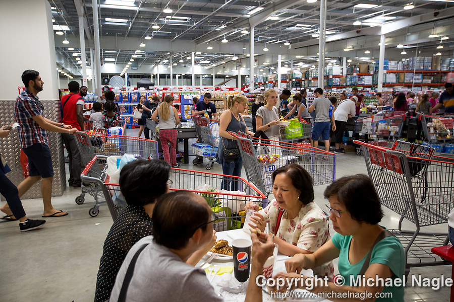 Costco Wholesale Corp. members eat at the food court in a newly opened Costco warehouse in Villebon-Sur-Yvette, France, on Saturday, July 7, 2018. The 150,000-square foot warehouse, which opened last month just outside of Paris, is Costco's first store in France. Costco plans to open 15 more warehouses in France by 2025. Photograph by Michael Nagle