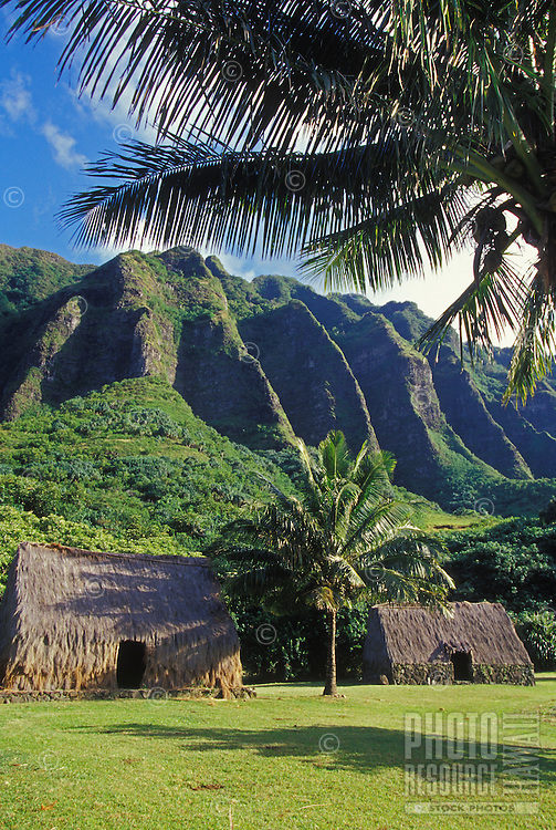 Traditional Hawaiian huts with crenelated mountain range at Kualoa Ranch, windward Oahu