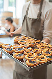 PORTUGAL, Lisbon, a baker is holding a tray filled with Pasteis de Nata, Portuguese typical Passtries