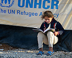 A girl reads a book outside her family's tent in the Zaatari Refugee Camp, located near Mafraq, Jordan. Opened in July, 2012, the camp holds upwards of 50,000 refugees from the civil war inside Syria. International Orthodox Christian Charities and other members of the ACT Alliance are active in the camp providing essential items and services.
