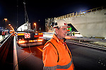 MAARN - Een medewerker van bouwcombinatie de Poort van Bunnik wacht tot de laatste wagen, na tijdelijk afzetten van de weg, 's avond voorbij rijdt, voordat hij verder gaat met het plaatsen van liggers van ecoduct Mollebos. Het 53 meter brede wildviaduct is één van de vele wildpassages die gelijktijdig met het verbreden en vernieuwen van de 30 km langs snelweg A12  Utrecht Lunetten â Veenendaal wordt aangelegd.  Bij het optakelen van een element werd telkens door verkeersbegeleiders van Rijkswaterstaat het verkeer even stil gezet. De bouwcombinatie bestaat uit BAM PPP, BAM Wegen, BAM Civiel en BAM Infratechniek. COPYRIGHT TON BORSBOOM