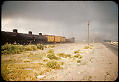 Freight train with tank cars, refrigerator cars, gondolas, caboose in Alamosa area along side highway.<br /> D&amp;RGW  Alamosa, CO