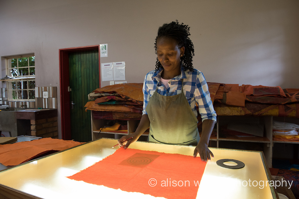 Africa, Swaziland, Malkerns. Nest organization artisan project.  Nest is partnering with Baobab Batik & local artisans to help market their batik products to global markets and better sustain their local community. Longile Ginindza, waxer, working with stencils. Has worked here 5 years, has one 9 year old child.