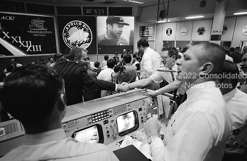 "Houston, TX - (FILE) -- Donald K. ""Deke"" Slayton (in black shirt, left of center) director of flight crew operations, and Chester M. Lee shake hands in Mission Control, while Rocco Petrone watches Apollo 13 commander Jim Lovell on the screen following their successful landing in the Pacific Ocean on April 17, 1970.  This photo is part of the book ""Apollo: Through the Eyes of the Astronauts"" published to commemorate the 40th anniversary of the first manned lunar landing on July 20, 1969..Credit: NASA via CNP"