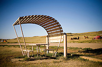 A curved picnic shelter stands in a campground at Badlands National Park in South Dakota, USA.