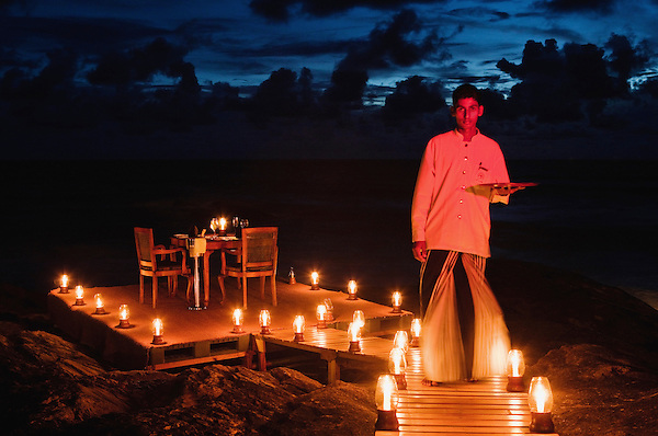 A waiter lights candles and sets a table for two for a romantic dinner on the beach, one of the special guest offerings at Saman Villas, Aturuwella, Bentota, Sri Lanka.