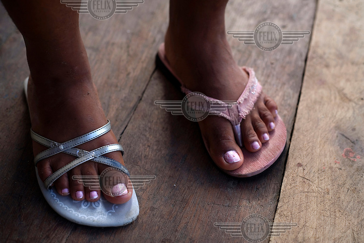 A woman wearing two different sandals on a wooden deck on the island of Limones.