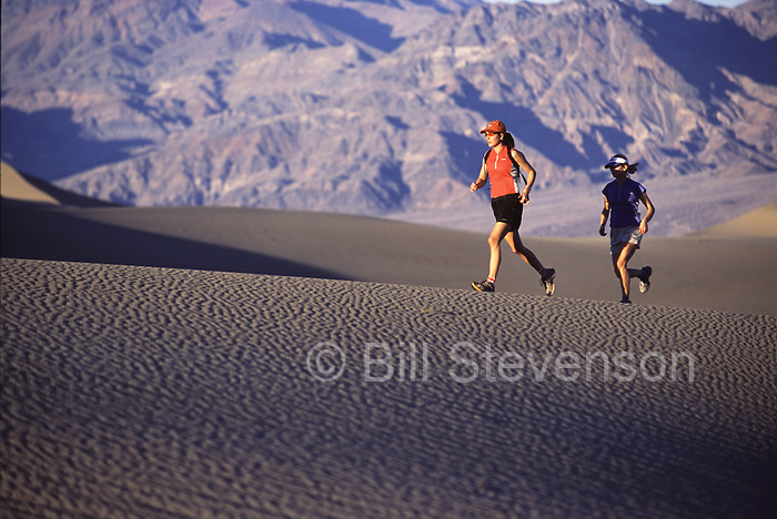 A picture of two women running on a sand dune in Death Valley, CA.