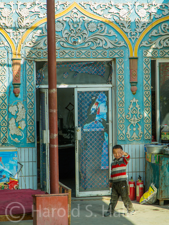 A child waves goodbye to our bus leaving a mosque near Turpan, China