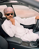 OMAN, Muscat, young man in traditional clothing sitting in his car
