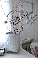 A hazel branch decorated with Christmas ornaments brings a festive feel to this child's bedroom