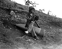 Using an unexploded 16-inch naval shell for a resting place, Marine Pfc. Raymond Hubert, shakes a three-day accumulation of sand from his boondocker.  Saipan, July 4, 1944.  S.Sgt. A.B. Knight.  (Marine Corps)<br /> NARA FILE #:  127-N-85221<br /> WAR & CONFLICT BOOK #:  875