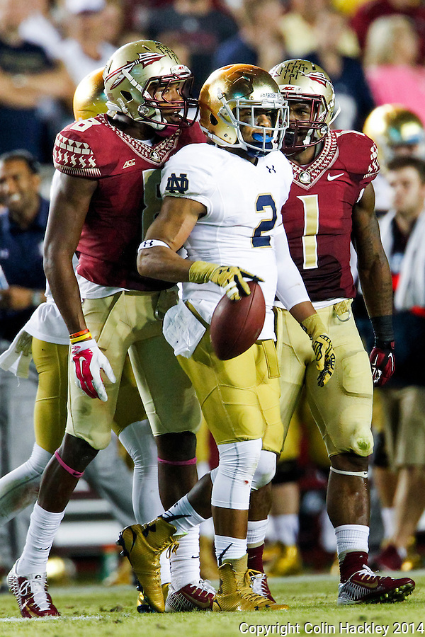 TALLAHASSEE, FLA. 10/18/14-FSU-ND101814CH-Florida State's Jalen Ramsey, left, and Ermon Lane bend the ears of Notre Dame's  Chris Brown during second first half action Saturday at Doak Campbell Stadium in Tallahassee. The Seminoles beat the Fighting Irish 31-27.<br /> COLIN HACKLEY PHOTO
