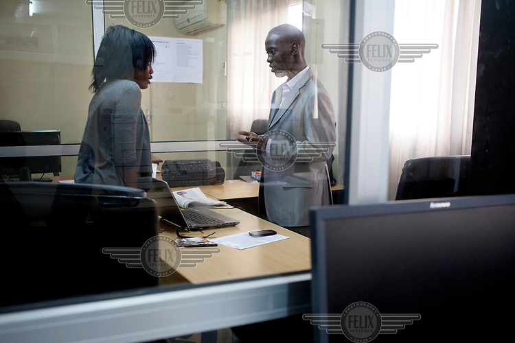 Daoude Mine, Editor in Chief of L'Observateur, speaks with a colleague in his office.