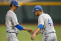UCLA pitcher Adam Plutko (9) is greeted by teammate Ryan Deeter (40) after he was removed during Game 1 of the 2013 Men's College World Series Finals against the Mississippi State Bulldogs on June 24, 2013 at TD Ameritrade Park in Omaha, Nebraska. The Bruins defeated the Bulldogs 3-1, taking a 1-0 lead in the best of 3 series. (Andrew Woolley/Four Seam Images)