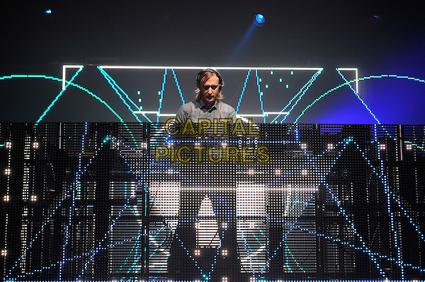 David Guetta.Performing at the BBC Radio1 Hackney Weekend, Hackney Marshes, London, England. .24th June 2012.on stage in concert live gig performance music full length grey gray shirt facial hair beard headphones .CAP/MAR.© Martin Harris/Capital Pictures.