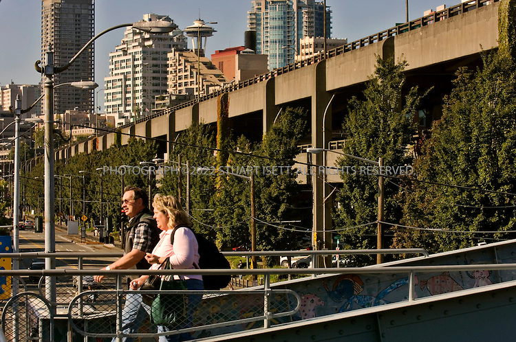 9/12/2006--Seattle, WA, USA..The double tiered Alaskan Highway Viaduct running along Seattle's waterfront as commuters head to the catch ferries. Originally built in the 1950s, the viaduct was damaged in the 2001 Nisqually earthquake. Three plans have been offered to replace the damaged road with a tunnel, with a new viaduct or to remove the road completely and restore Seattle's waterfront...Photograph By Stuart Isett.All photographs ©2006 Stuart Isett.All rights reserved.
