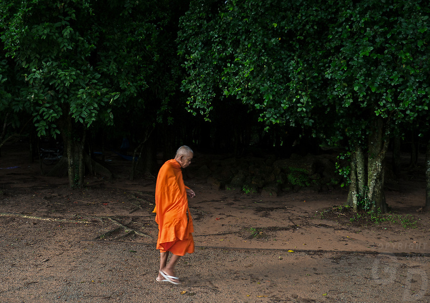 Older Buddhist Monk walking the path near Angkor Wat, Cambodia