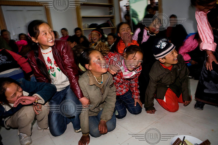 Khampa children laugh as they play games in a town in the far west of the province.