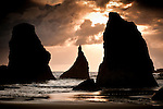 Seastacks are silhouetted during a moody sunset along the southern Oregon coastline.