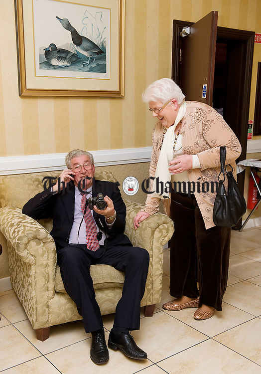 Sixmilebridge's Sean Collins on the phone as his wife Marian waits  at the 50th anniversary celebration of the Clare ploughing Association in the Clare Inn Hotel. Photograph  by John Kelly.