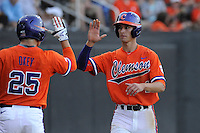 Shortstop Eli White (4) of the Clemson Tigers is congratulated by catcher Chris Okey after scoring a run in a game against the Wofford College Terriers on Tuesday, May 5, 2015, at Russell C. King Field in Spartanburg, South Carolina. Wofford won, 17-9. (Tom Priddy/Four Seam Images)