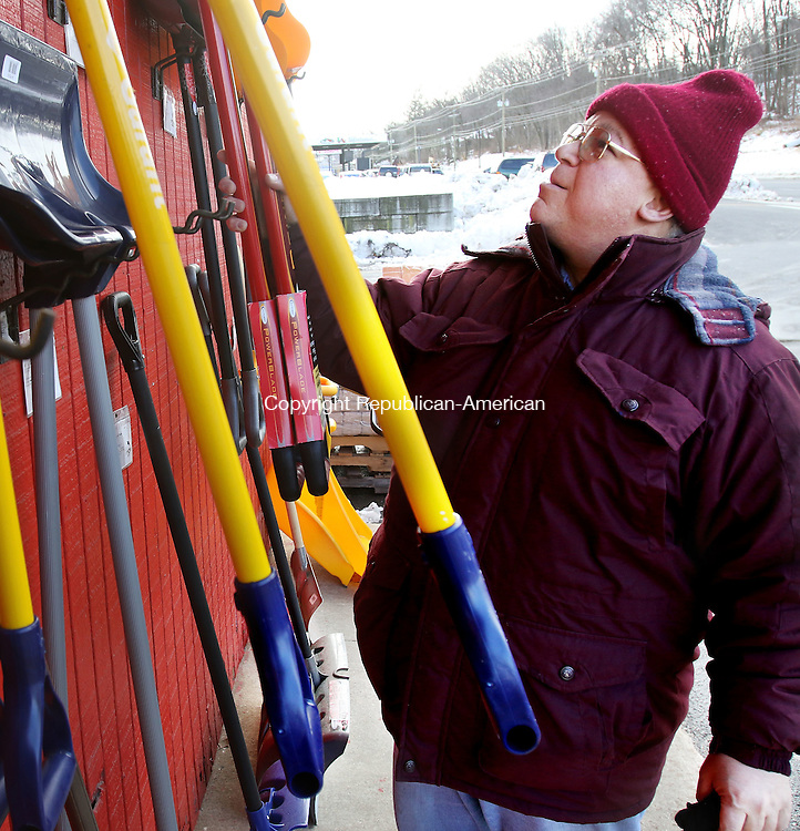 WATERBURY CT. 25 January 2017-012517SV08-John Giudice arranges snow shovels outside Schmidt's &amp; Serafines True Value Hardware in Waterbury Wednesday. Weeks of 50-degree days and snow days far and few between has made for a harsh winter for the businesses that depend on it to sell shovels, snow blowers and ice melt, as well as home heating businesses. Area merchants are hoping for a frigid, snowy February. <br /> Steven Valenti Republican-American