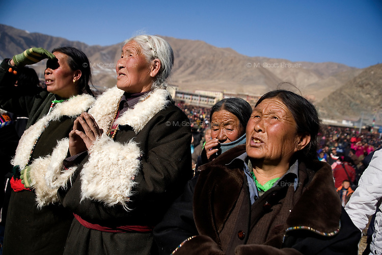 Tibetan Buddhist pilgrims gather to give money and prayer goods to monks during the Monlam Festival at the Labrang Monastery in Xiahe, Gansu, China.  The monks are gathered around the annual thangka presentation, an hour long display of a gigantic painted tapestry of Buddha displayed on a hillside.