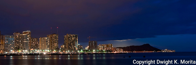 Daimond Head in profile next to evening skyline of Waikiki. Full moon behind clouds adds the lighting that brings Diamond Head into relief.