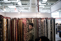 A merchant adjusts samples of the textiles he sells as part of a display at the Keqiao World Trade Center in Keqiao, Shaoxing County, Zhejiang, China, during the Keqiao International Textiles, Fabrics & Accessories Exhibition 2008.  Shaoxing County is one of China's biggest producers of textiles.