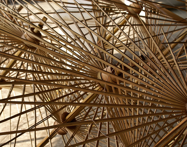 Completed parasol frames stacked ready to be covered with silk create an interesting geometric design. The framework is hand constructed in assembly-line fashion from bamboo and after a silk covering is applied they are hand-painted in beautiful designs.