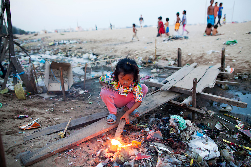 A girl stokes a make-shift fire near a drainage canal on the edge of Boeung Kak lake, which has been filled in with sand, Phnom Penh, Feb 4, 2011.
