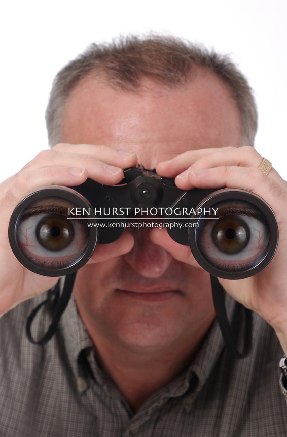 man looking through binoculars with magnified cartoon eyes in the lenses; isolated on white; see two other versions, one normal, one with less effect