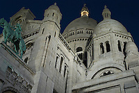 Sacre Coeur at Night.  Montmartre, Paris.  Nighttime, natural light shot of the Sacre Coeur Basilica at the top of Montmartre.  Lighting is from the monument's spotlights.  Notice the light in the top spire.  Because of its rounded towers with a amall point, some locals call it the Italian Ice Cream church (think soft serve ice cream...)