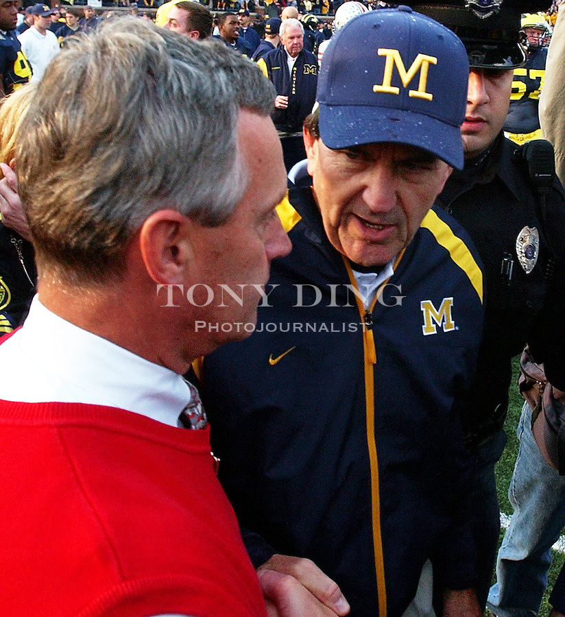 Michigan head coach Lloyd Carr shakes hands with Buckeye's head coach Jim Tressel after the Wolverine's 35-21 upset of Ohio State on Saturday, November 22, 2003 in Ann Arbor, Mich. This was the 100th rivary match between UM and OSU. This is Tressel's first loss to Michigan after he took over as OSU coach in 2001. (TONY DING/The Michigan Daily)
