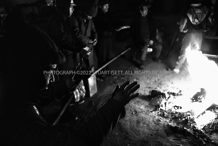 Osaka, Japan..Homeless men gather around a fire in Osaka's Kamagaseki neighboorhood to warm tghemselves up on a winter's evening...All photographs ©2003 Stuart Isett.All rights reserved.This image may not be reproduced without expressed written permission from Stuart Isett.