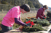 NWA Democrat-Gazette/DAVID GOTTSCHALK Cheryl Tyson (left) removes the bows from wreaths Friday, March 9, 2018, during the the 6th annual Wreath Recycling Project for Bo's Blessings at the Arkansas National Guard Armory in Fayetteville. Bo's Blessings LUTHAB, Inc., collects and then removes the wiring and bows on more than 8,500 wreaths that were distributed on the grave sites at the Fayetteville National Cemetery. The greenery will be used mulch and wire will be collected by the city of Fayetteville Recycling and Trash Collections.