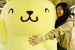 A woman squeezes a Sanrio's character Pom Pom Purin or Purin plush dolls displayed along in the Tokyo Metro Promenade on March 8, 2016, Tokyo, Japan. 11 of the huge cuddly characters will be displayed in an underground passage of Shinjuku Station until March 13, as a part of the celebrations for the 20th Birthday of Pom Pom Purin. Sanrio is a Japanese company established in 1963, which has created over 400 cute characters, including the worldwide known Hello Kitty. (Photo by Rodrigo Reyes Marin/AFLO)
