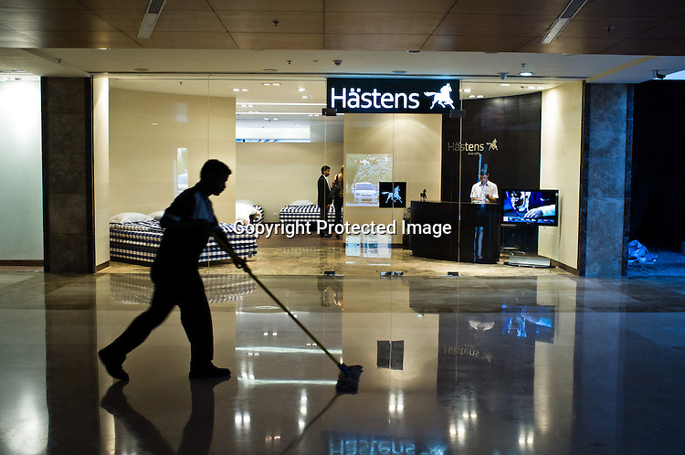 A cleaner sweeps the floor outside the newly opened Hästens luxury beds retail store in Select City Walk Mall in New Delhi, India. Photo: Sanjit Das