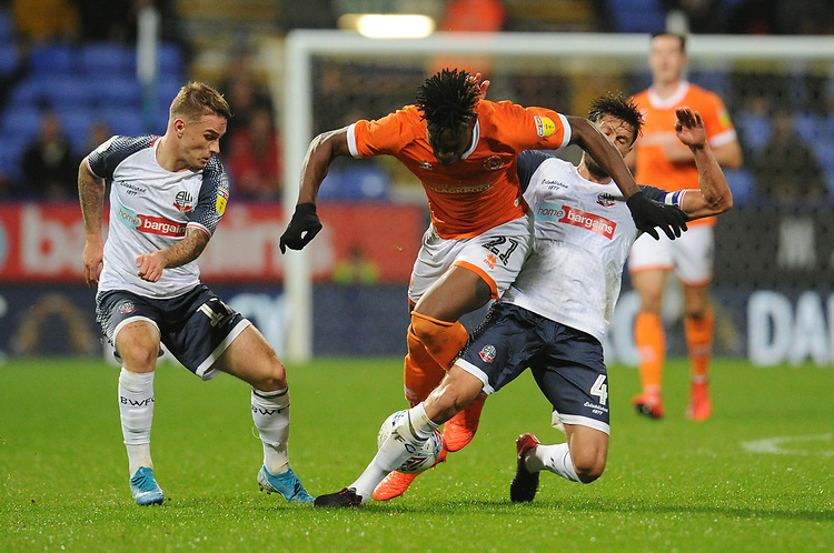 Blackpool's Armand Gnanduillet is tackled by Bolton Wanderers' Jason Lowe<br /> <br /> Photographer Kevin Barnes/CameraSport<br /> <br /> The EFL Sky Bet League One - Bolton Wanderers v Blackpool - Monday 7th October 2019 - University of Bolton Stadium - Bolton<br /> <br /> World Copyright © 2019 CameraSport. All rights reserved. 43 Linden Ave. Countesthorpe. Leicester. England. LE8 5PG - Tel: +44 (0) 116 277 4147 - admin@camerasport.com - www.camerasport.com