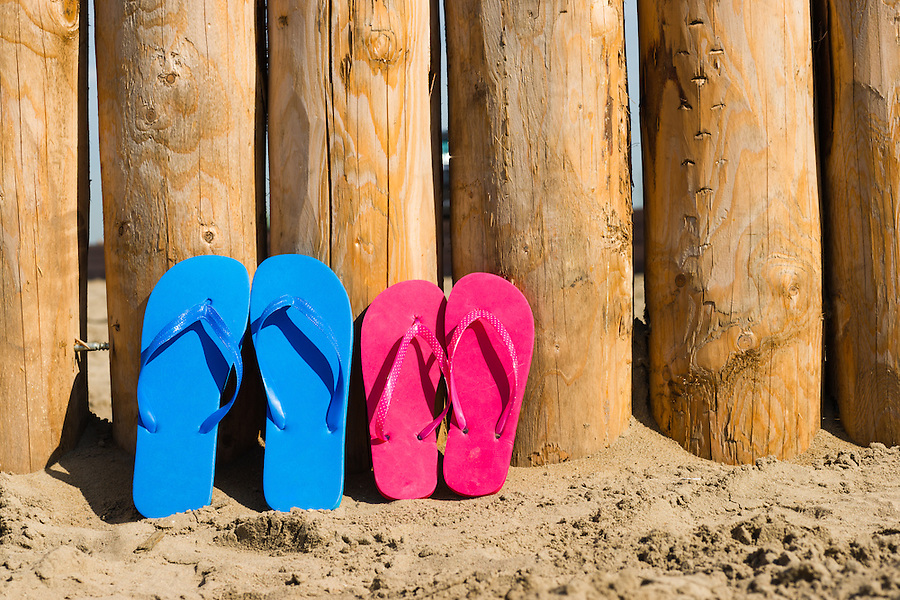 wheathered wood on the beach and some slippers