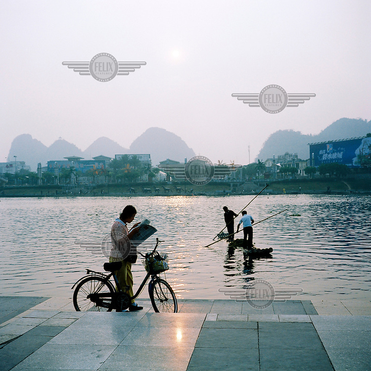 A man reads a newspaper on his bicycle by the river in Guilin.