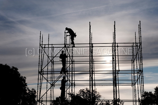 Workers on scaffoldings building up the open air display for the Breda Photo festival in the Chassé Park (Netherlands, 19/09/2008)