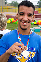Proud happy athlete displaying his winning medal. Special Olympics U of M Bierman Athletic Complex. Minneapolis Minnesota USA